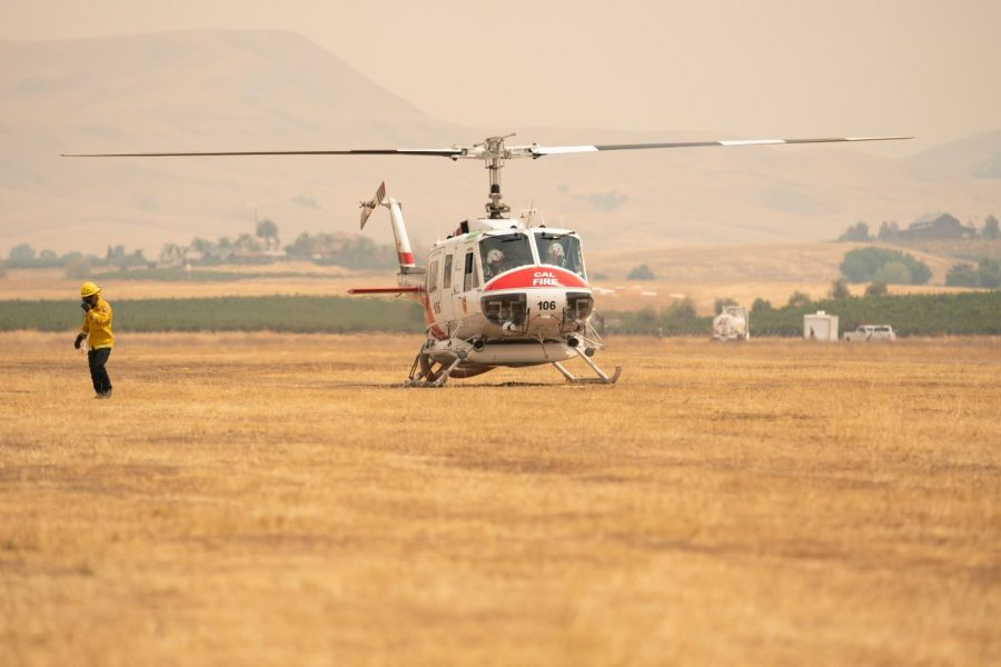 Ground crew clears the area as a transport Huey leaves Meadowlark field with firefighters bound for the SCU Lightning complex fires.